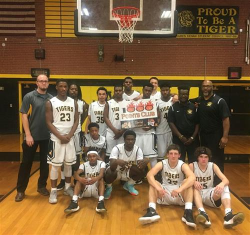The JKHS Tiger Men's basketball team celebrates McCaster's milestone.