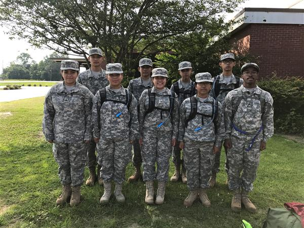 A group of cadets stand proudly in their JROTC army green camo uniforms