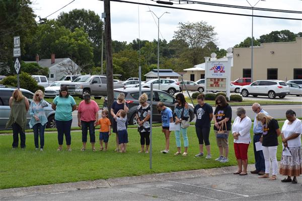 Attendees bow their heads in prayer at the annual Prayer at the Flagpole