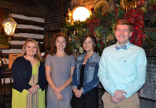Four Rotary Students of the Month stand in front of the fireplace at the Country Squire Restaurant