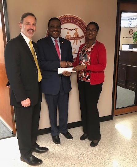 Superintendent Dr. Austin Obasohan (center) accepts a donation from Edie Gleaves (left) and Pat Litzinger.