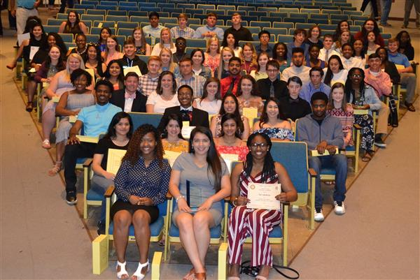 Seniors at the M. Austin Carter Academic Ceremony proudly display their trophies.