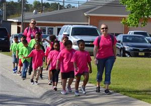 First graders and their teachers, dressed in bright pink and green, walk toward the Board of Educ.