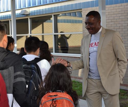 Dr. O gives students high fives on the first day of school